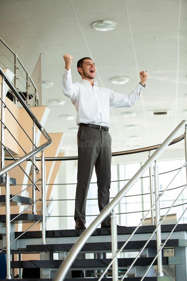 庆祝成功 激动的年轻商人保持胳膊被举和表达阳,当站立用办公室时 库存照片