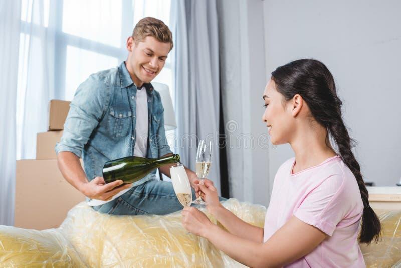 庆祝搬入新的家的愉快的年轻夫妇 库存照片