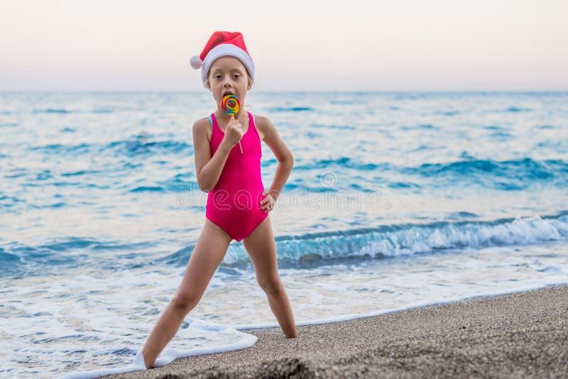 庆祝新年和圣诞节在海滩的逗人喜爱的女孩在圣诞老人项目帽子,自由空间 库存照片