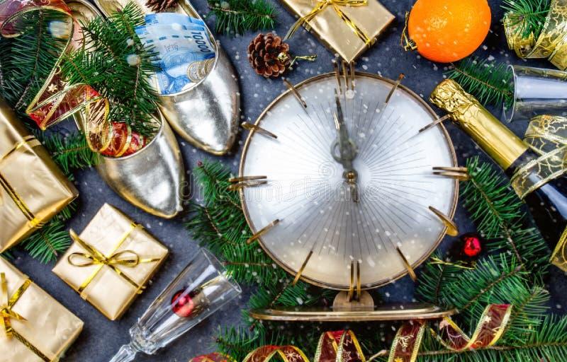 庆祝新年度 穿上鞋子的传统被投入的金钱为有金钱en新年 与葡萄酒时钟的平的位置构成 库存图片