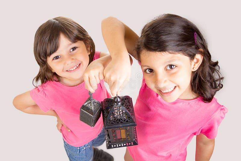 庆祝有他们的灯笼的2个逗人喜爱的愉快的女孩赖买丹月 免版税库存图片