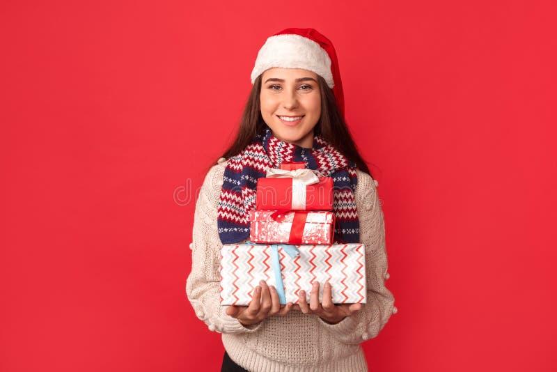 庆祝概念查出的白色 在与礼物盒微笑的红色围巾和圣诞老人帽子身分的年轻女人隔绝的快乐 免版税图库摄影