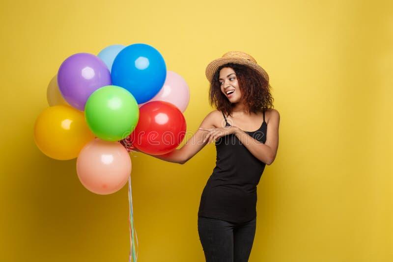 庆祝概念-接近的黑T恤杉的画象愉快的年轻美丽的非洲妇女微笑与五颜六色的党的 免版税库存照片