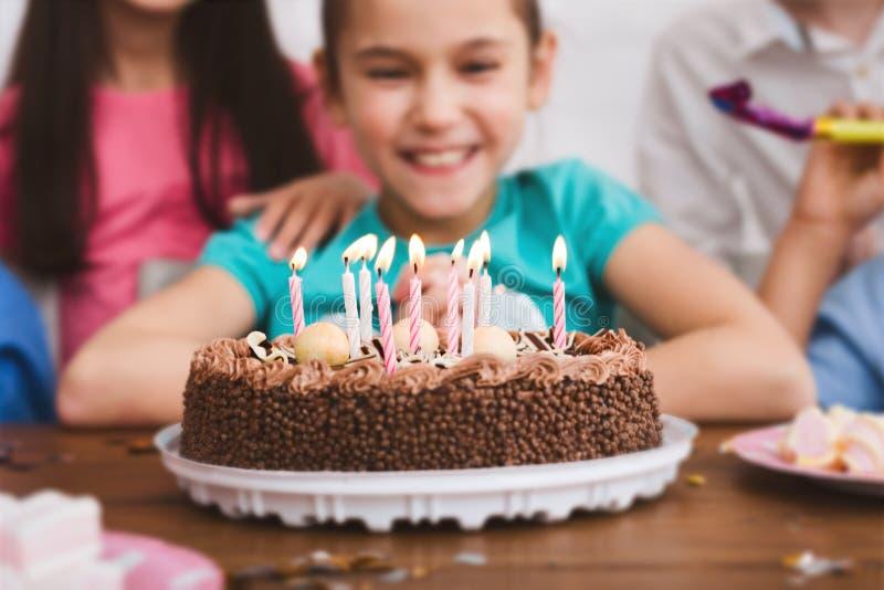 庆祝生日和吹在蛋糕的可爱的女孩蜡烛 库存照片