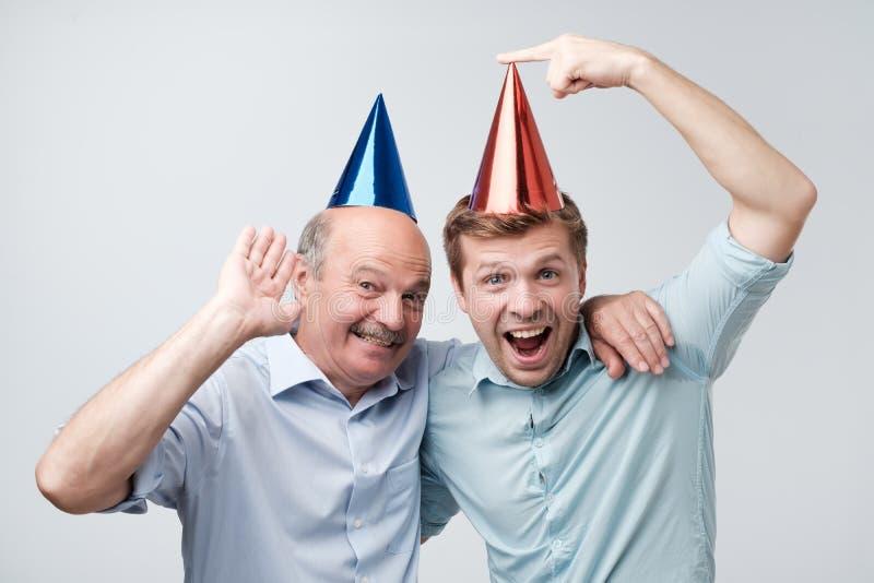 庆祝生日或其他家庭假日的父亲和儿子 他们是愉快看他们的客人 库存照片