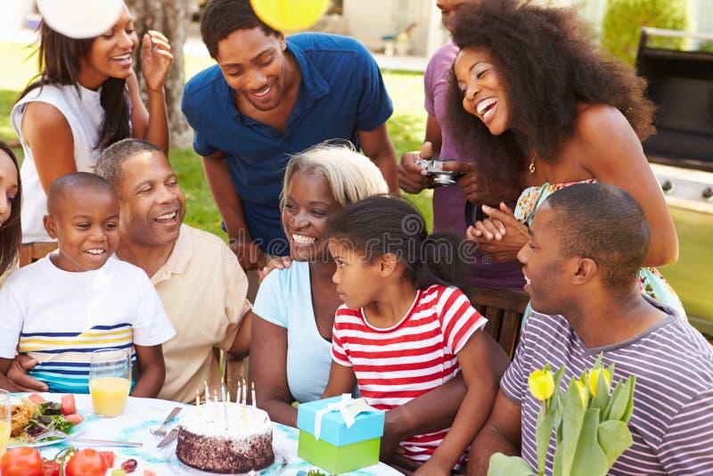 庆祝生日的多一代家庭在庭院里 免版税库存图片