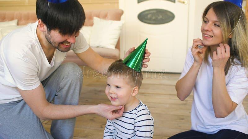 庆祝生日的愉快的家庭的父亲在家投入在帽子对他的儿子 图库摄影