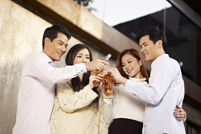 庆祝用啤酒的亚裔年轻人 免版税库存照片