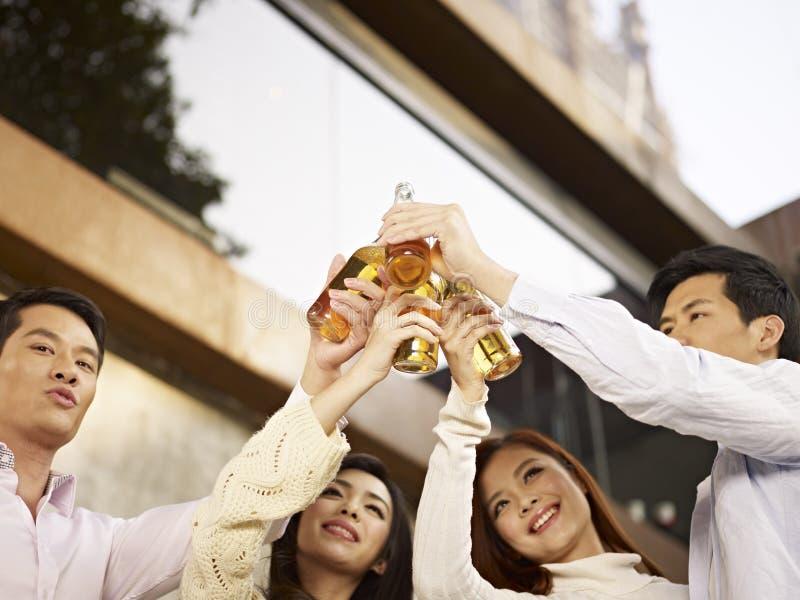 庆祝用啤酒的亚裔年轻人 免版税图库摄影