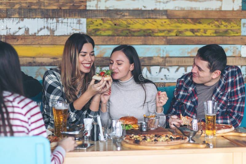 庆祝用比萨和啤酒的愉快的年轻朋友在酒吧餐馆 免版税库存照片