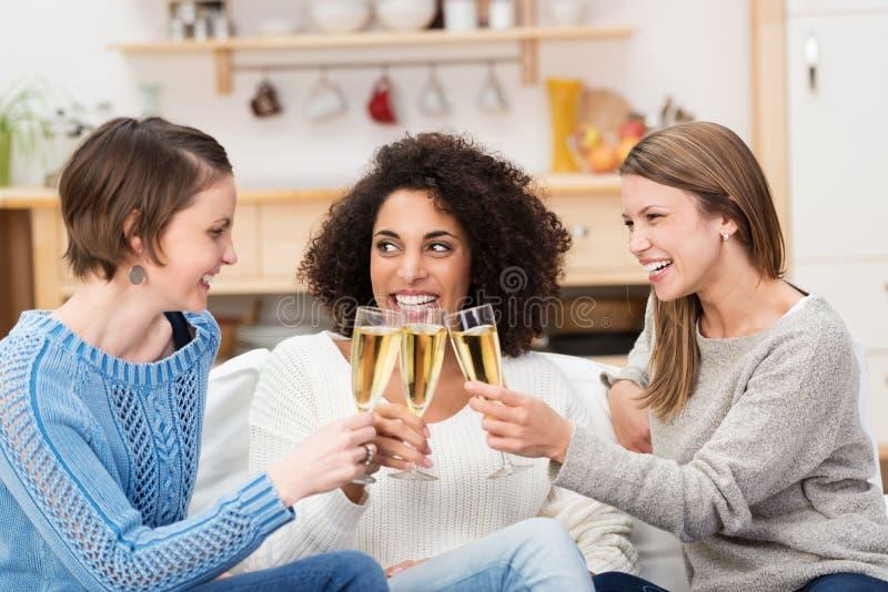 庆祝用香槟的三名可爱的妇女 免版税库存照片