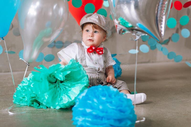 庆祝第一个生日的哀伤的男婴 用气球和五颜六色的横幅装饰的孩子生日宴会 库存图片