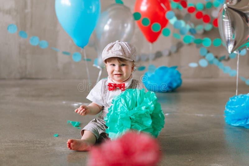 庆祝第一个生日的哀伤的男婴 用气球和五颜六色的横幅装饰的孩子生日宴会 免版税库存图片
