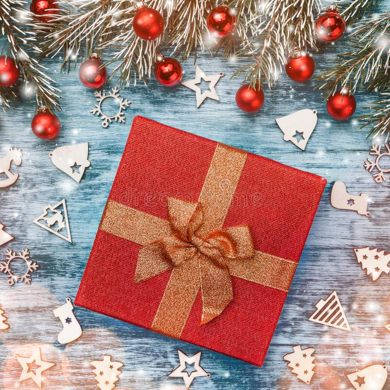庆祝结构的圣诞节礼物、冷杉分支、红色中看不中用的物品和木被装饰的玩具在天蓝色的背景 免版税库存图片