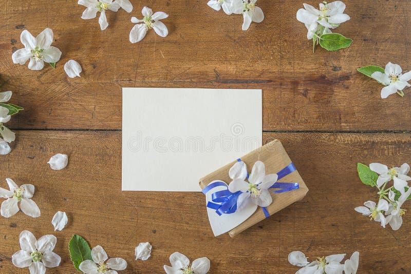 庆祝背景:手工制造礼物盒、纸和苹果开花在葡萄酒木背景 免版税库存照片