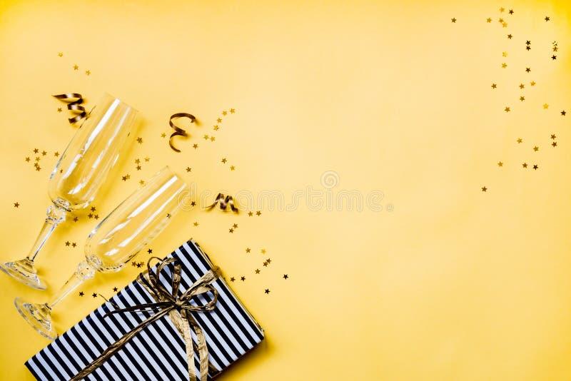 庆祝背景-两块chrystal香槟玻璃顶视图,在黑白有斑纹的纸包裹的礼物盒,丝带 免版税库存照片