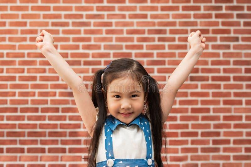 庆祝胜利用她的手的愉快的女孩被举以砖墙 库存图片