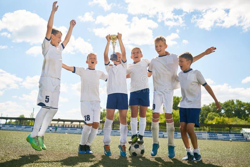庆祝胜利的小字辈橄榄球队 库存照片