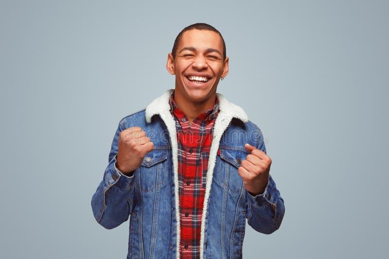 庆祝胜利的快乐的黑人 免版税库存照片