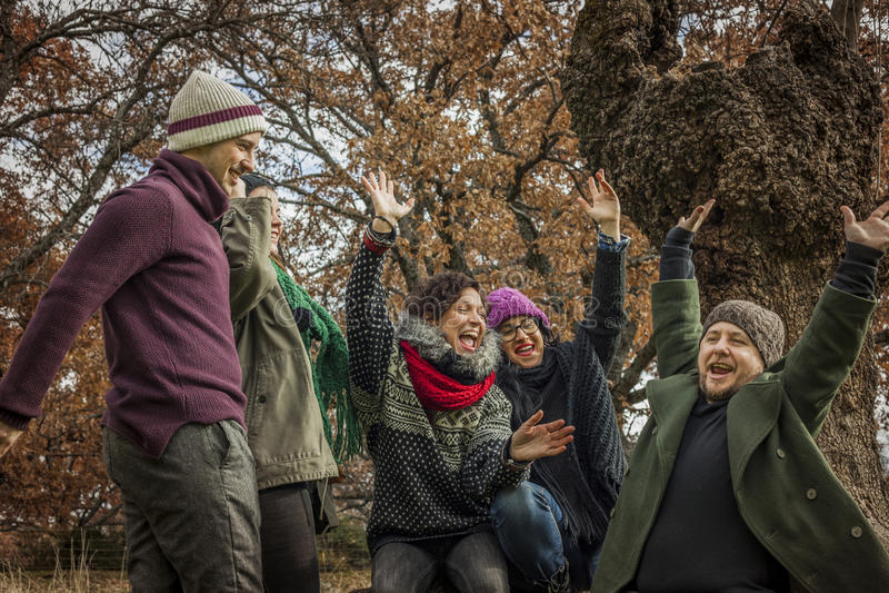 庆祝胜利的朋友配合在公园 免版税库存照片