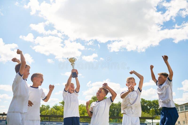 庆祝赢取的小字辈橄榄球队 免版税库存照片