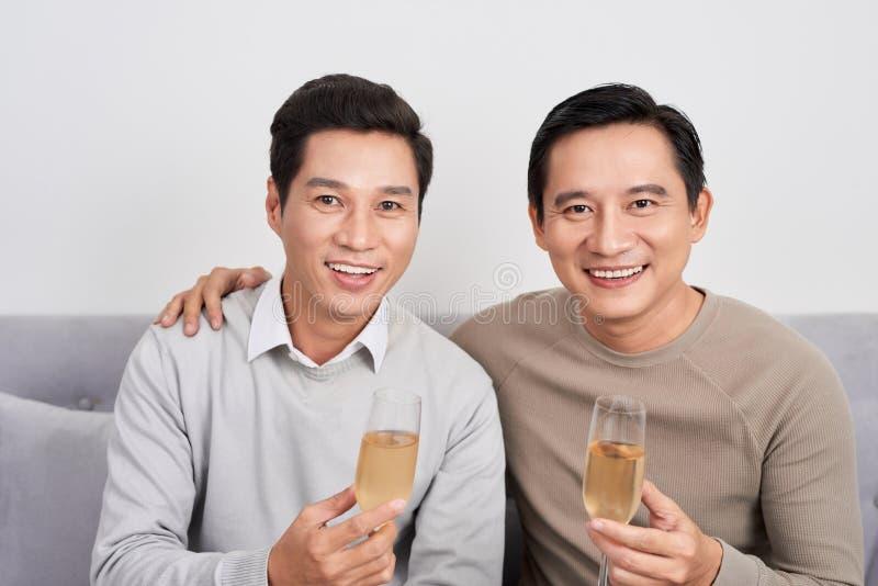 庆祝饮用的汽酒和正面的愉快的朋友人谈论,当坐家庭沙发时 免版税库存照片