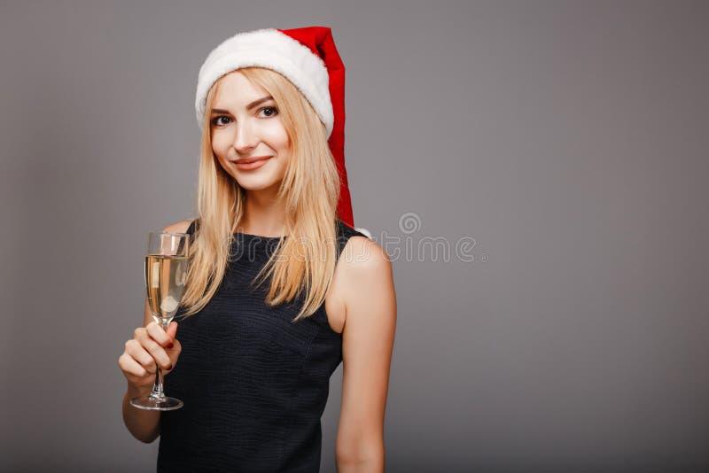 庆祝饮用的香槟的愉快的少妇 免版税库存照片