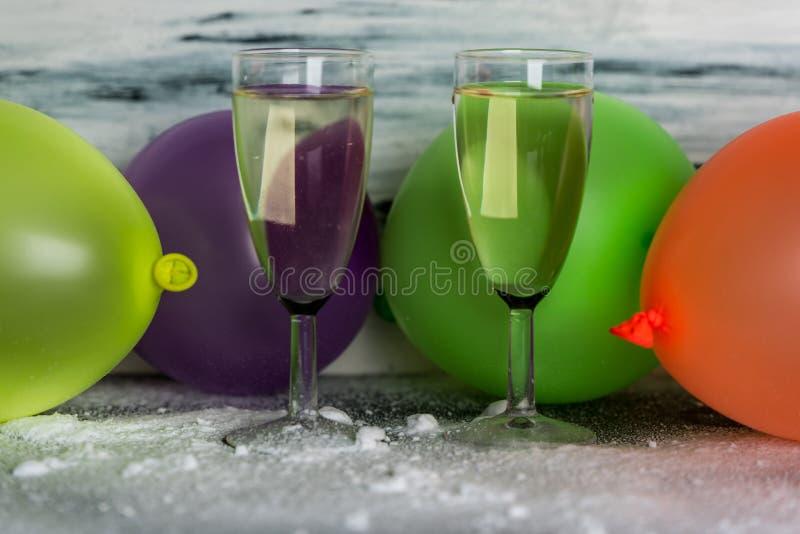 庆祝-两杯在色的气球背景的香槟  库存图片