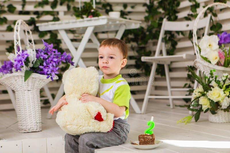 庆祝他的生日的愉快的小孩男孩拿着蛋糕,室内 子项的生日聚会 无忧无虑 免版税库存照片
