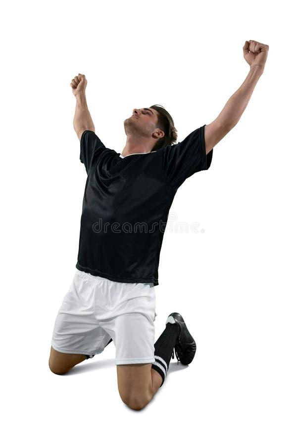 庆祝他的胜利的足球运动员 库存图片