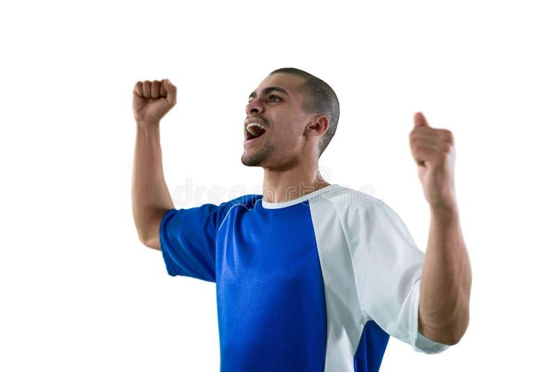 庆祝他的胜利的足球运动员 图库摄影