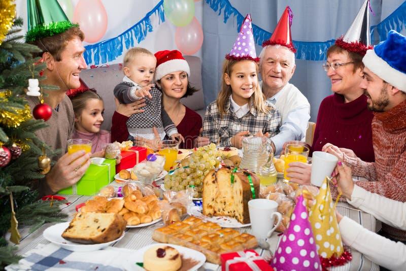 庆祝children's生日的家庭在欢乐晚餐期间 免版税库存图片