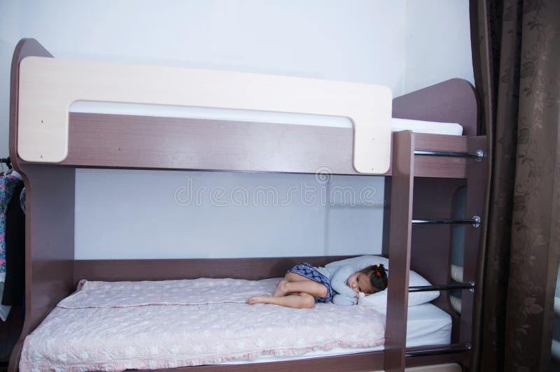床在儿童居室 说谎在床上的单独女孩 在内部的巧克力树荫与白色墙壁 库存照片