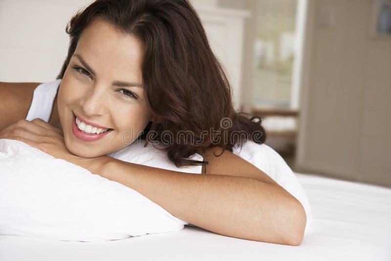 床微笑的轻松的妇女 免版税库存图片