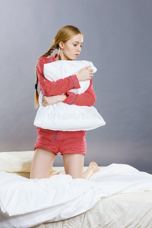 床扣人心弦的枕头的哀伤的沮丧的女孩 免版税库存图片