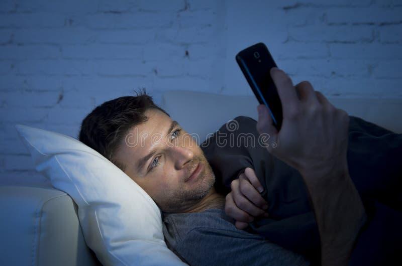 床长沙发的年轻人在使用手机的晚上在低灯在通讯技术概念后在家放松了 库存照片