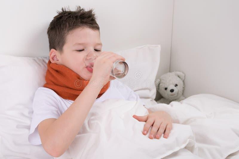 床饮用水的男孩在采取医学以后 免版税图库摄影