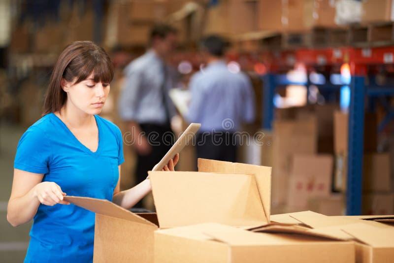 仓库复选框的工作者使用数字式片剂 免版税库存图片