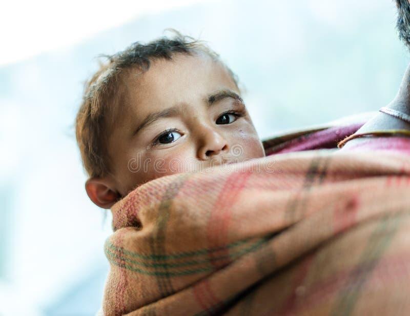 库尔卢,喜马偕尔邦,印度- 2018年12月21日:一个可怜的凝视的饥饿的印度男孩的特写镜头有哀伤的表示的在他的面孔 免版税库存照片