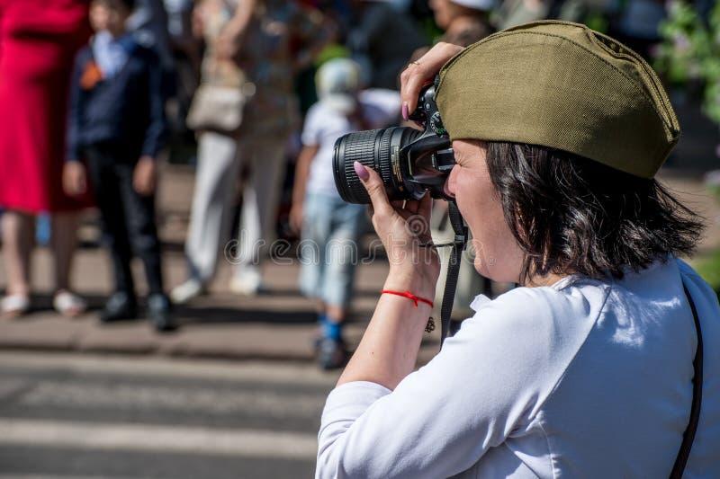 库尔斯克地区, ZHELEZNOGORSK,俄罗斯- 2018年5月9日 一个军用绿色盖帽的一个深色头发的俄国女孩画游行不朽的Regi 库存图片
