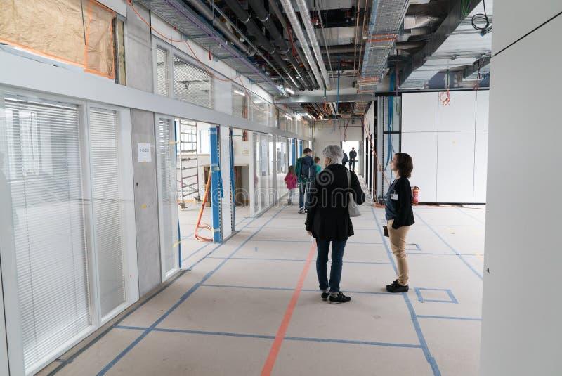 库尔,GR/瑞士- 2019年5月11日:访客与建筑工地的雇员聊天新的医院的在库尔  免版税库存照片