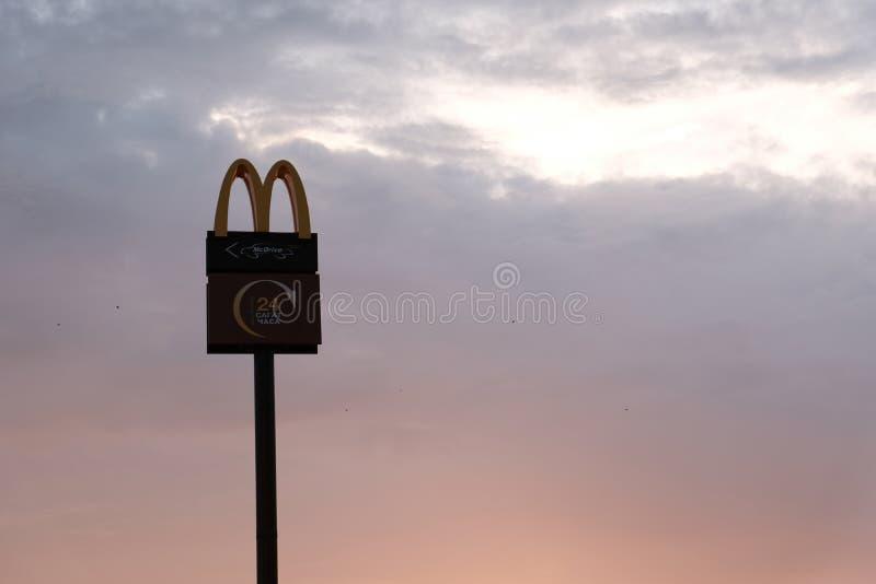 库斯塔奈,哈萨克斯坦,星期五2018年7月13日在柱子的,麦克唐纳` s商标高在天空在黎明或黄昏 剪影 复制空间 免版税库存照片