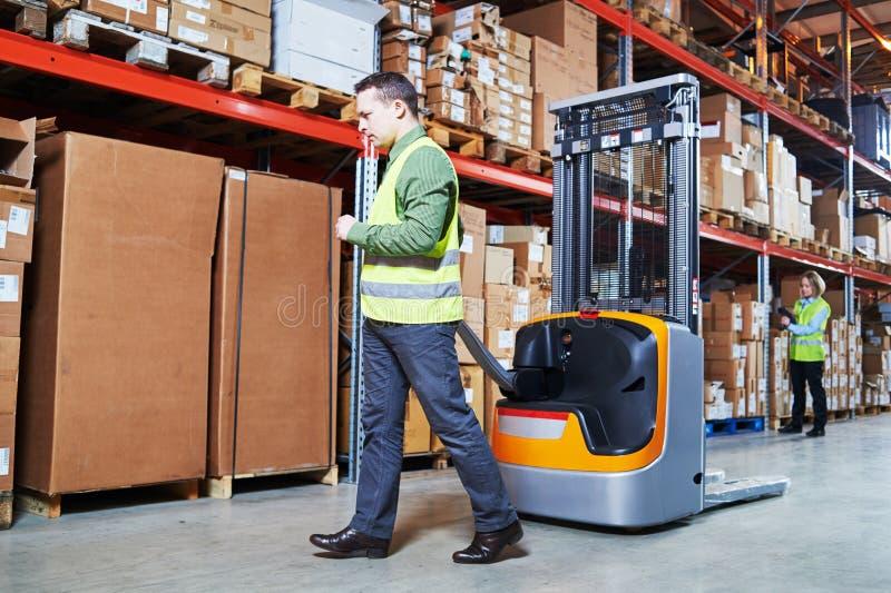仓库管理系统 有条形码扫描器和堆货机的工作者 免版税库存照片
