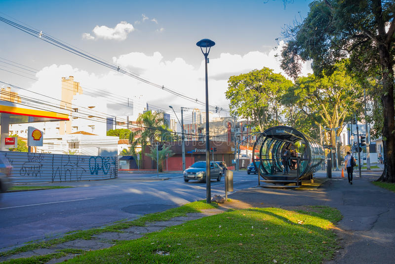 库里奇巴,巴西- 2016年5月12日:等待在驻地的乘客公共汽车,当有些汽车在街道时驾驶 库存照片