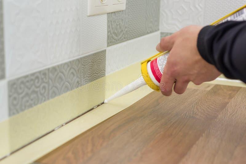 应用与建筑注射器的硅树脂密封胶 工作者填装在瓷砖在墙壁上和厨房worktop之间的缝 免版税库存图片