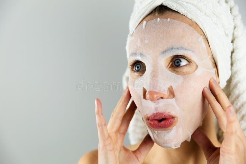 应用与润肤霜的美女面膜 免版税库存图片