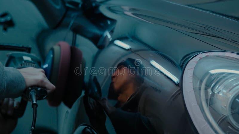 应用保护带的汽车波兰蜡工作者手在擦亮前 抛光的和擦亮的汽车 ( 人举行a polis 免版税图库摄影