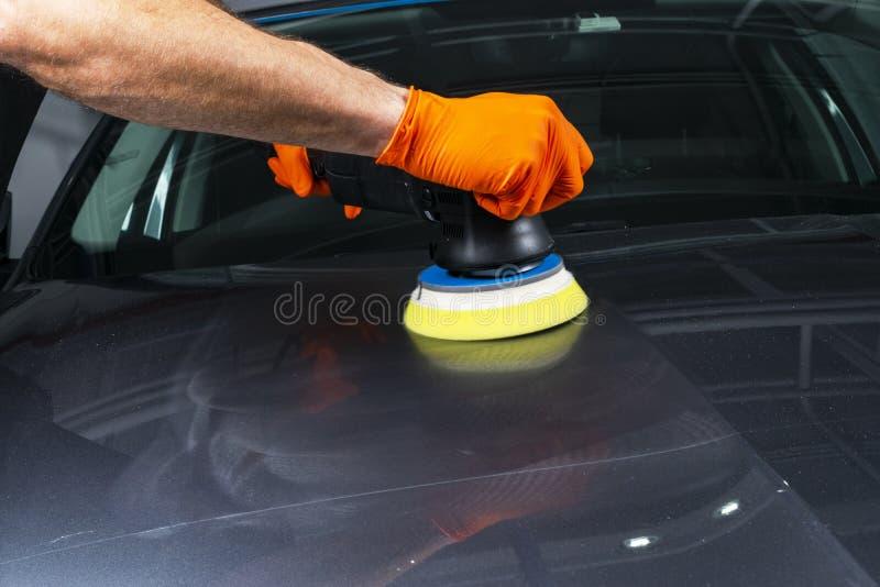 应用保护带的汽车波兰蜡工作者手在擦亮前 抛光的和擦亮的汽车 汽车详述 人举行a polis 免版税库存照片