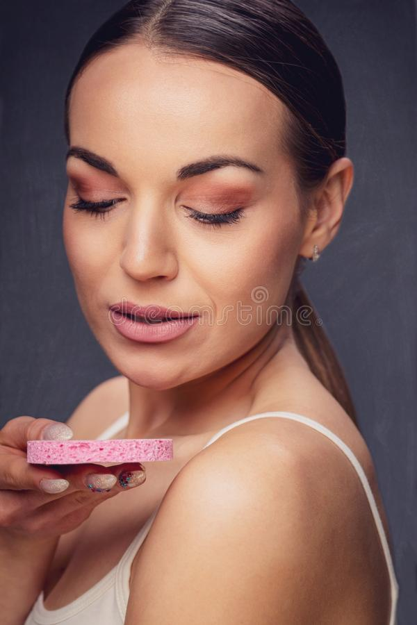 应用关心皮肤透明油漆 取消面孔构成的微笑的妇女使用化装棉 应用关心皮肤透明油漆 取消面孔构成的微笑的妇女使用化装棉 库存图片