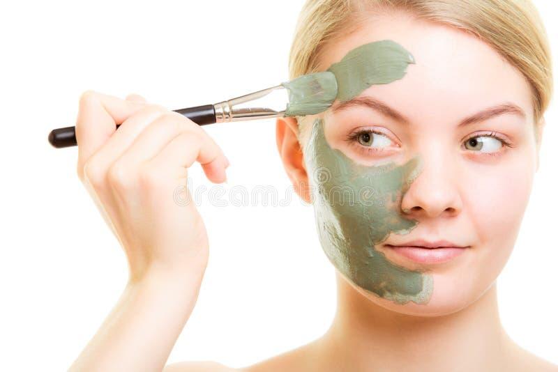 应用关心皮肤透明油漆 应用黏土在面孔的妇女泥面具 免版税库存照片